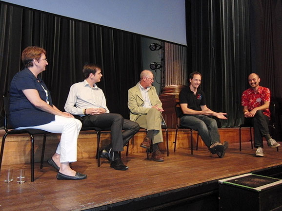 a panel of speakers on stage at ESC