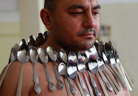 man with many spoons stuck to him