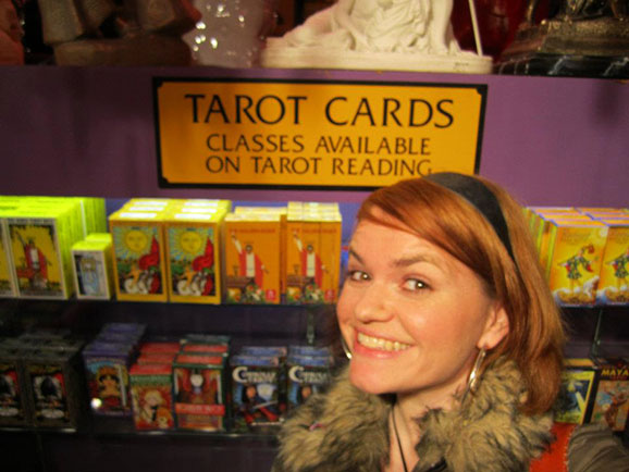the author in front of a sign for tarot cards and classes on readings